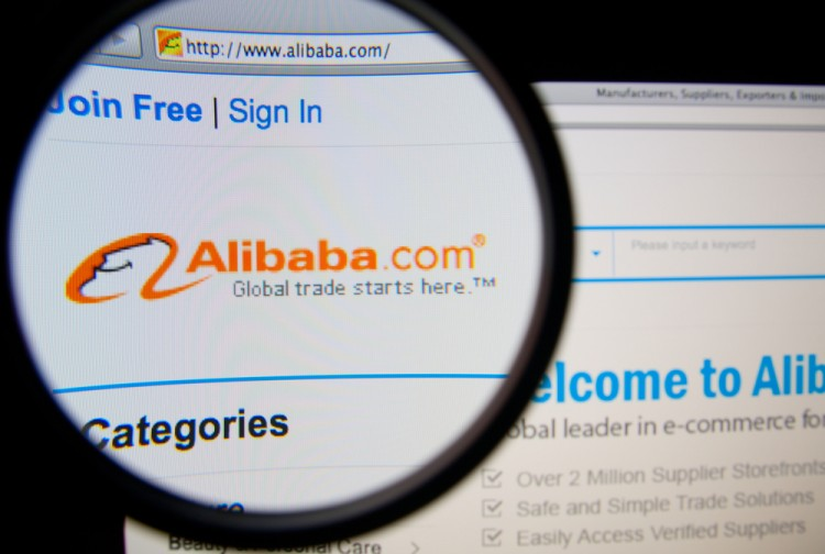 Alibaba Group Holding Ltd (NYSE:BABA), homepage on a monitor screen through a magnifying glass, retail, group, page